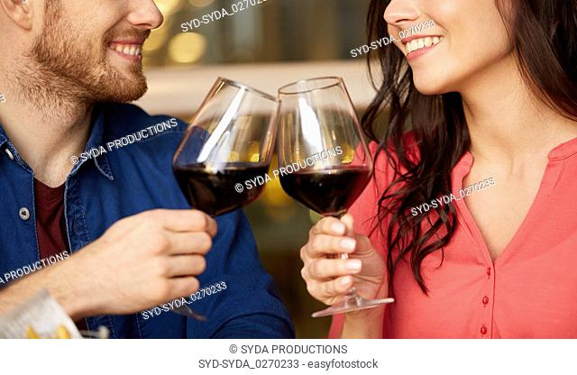 happy couple drinking red wine at restaurant