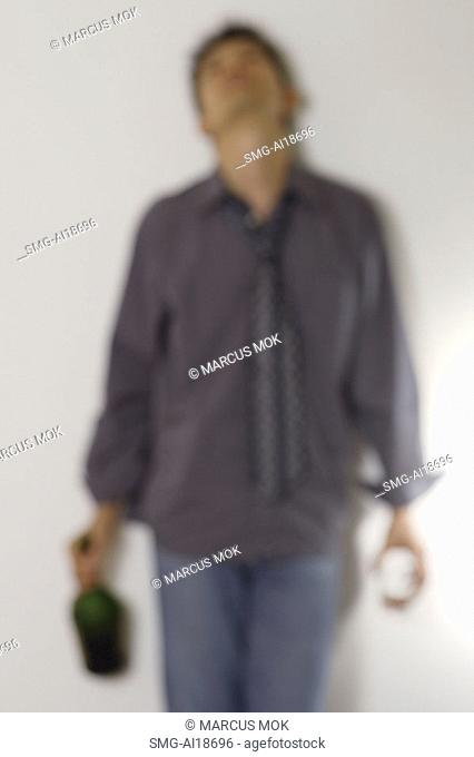 Man leaning against wall holding bottle and glass
