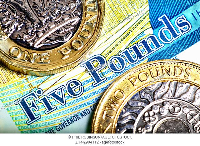 British £1 and £2 coins on a £5 note