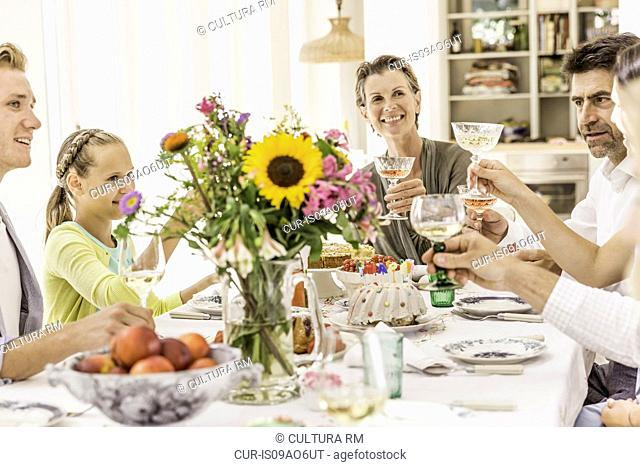 Family making champagne toast at birthday party table