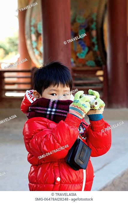 Young boy taking photo with Camera at Bulguksa Temple, Gyeongju Korea