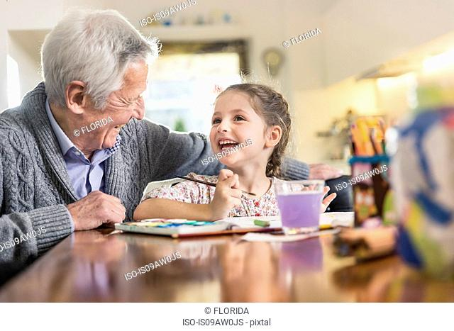 Senior man and granddaughter painting at kitchen table
