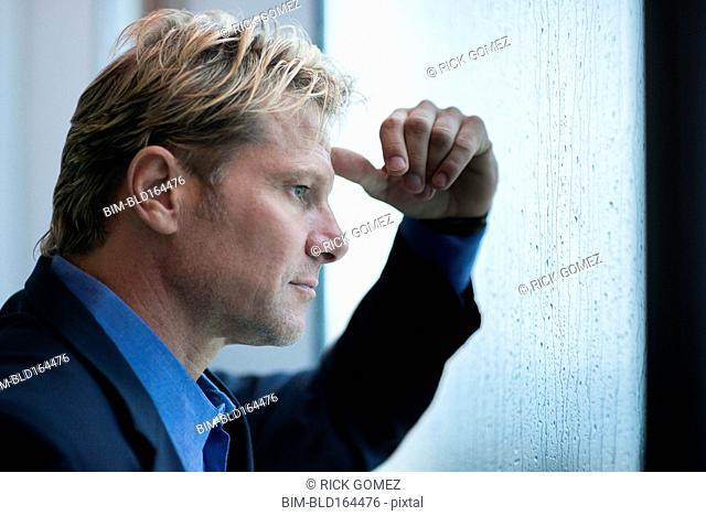 Caucasian businessman standing at rainy office window