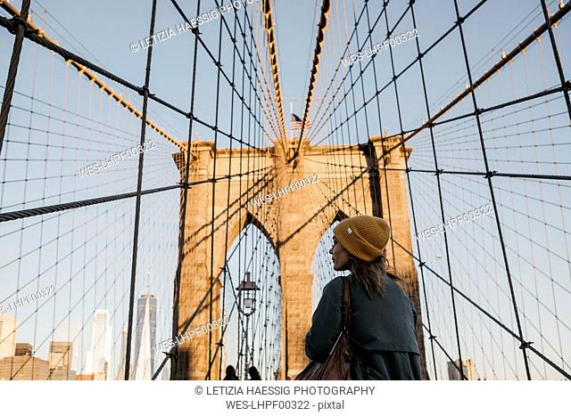 USA, New York, New York City, female tourist on Brooklyn Bridge in the morning light
