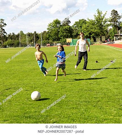 Father with children playing football