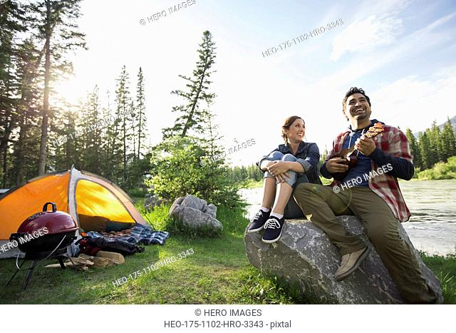 Couple playing ukulele at campsite