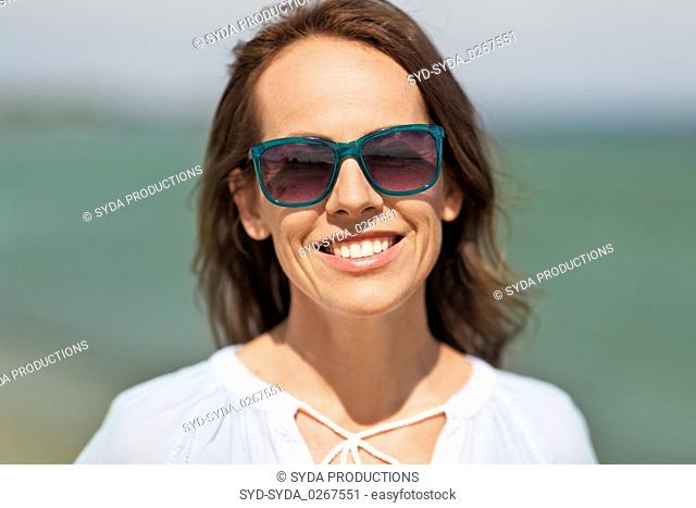 happy smiling woman in sunglasses on summer beach