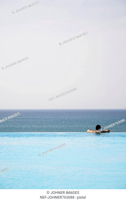 Man in a swimming-pool looking at the ocean, Greece