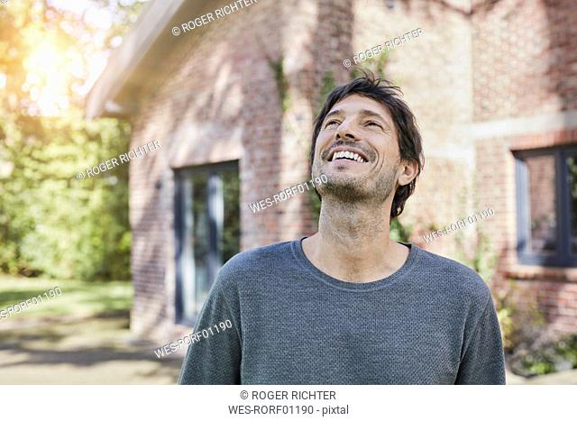 Portrait of happy man in front of his home