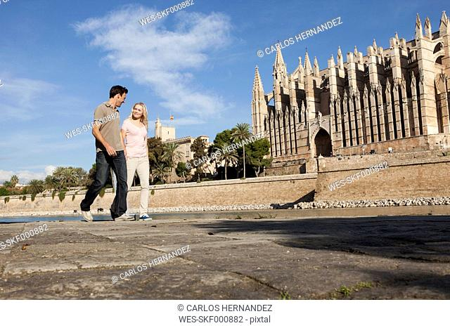 Spain, Mallorca, Palma, Couple walking with St Maria Cathedral in background