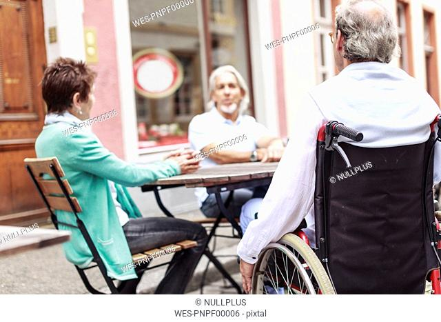 Germany, Heidelberg, senior man in wheelchair with friends in a street cafe