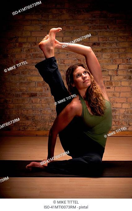 Woman practicing yoga on mat