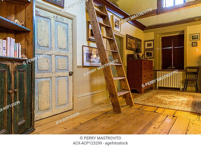 View of hallway with wide pinewood floorboards, bookcase, Miller's stairs and distressed bedroom doors on the upstairs floor inside an old circa 1805 Canadiana...