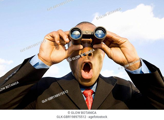 Close-up of a businessman looking through binoculars and looking shocked