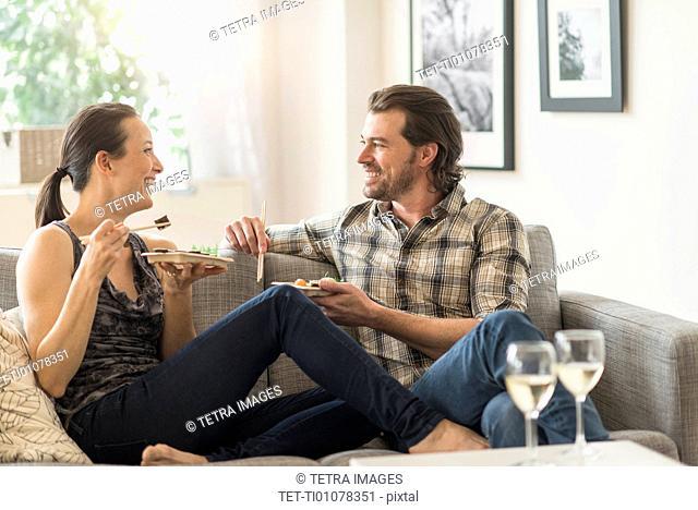 Cheerful couple eating on sofa