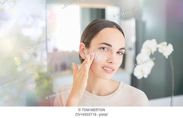 Portrait brunette woman applying face moisturizer to cheek