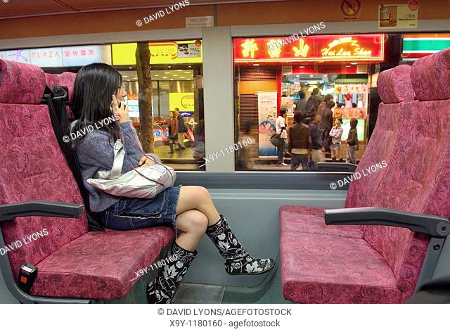 Downtown, Hong Kong, China  Young woman using mobile phone on bus outside cafes in Nathan Road, Tsim Sha Tsui district, Kowloon