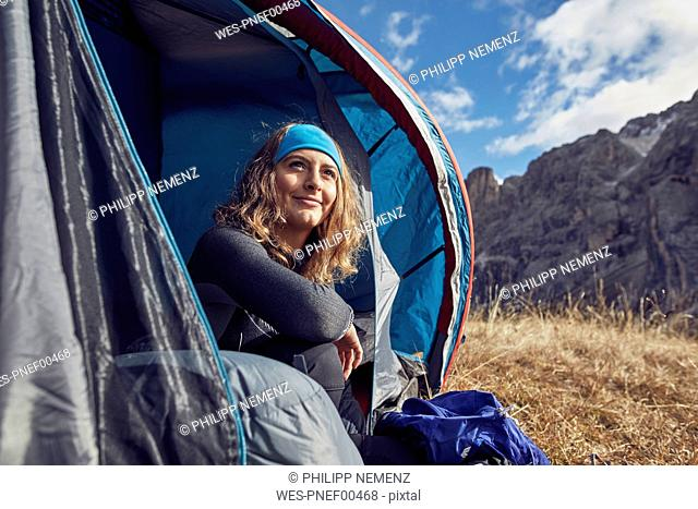 Smiling young woman sitting in tent in the mountains