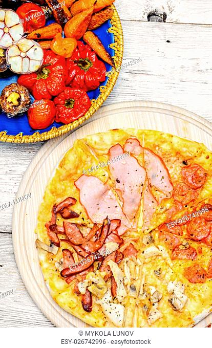 Pizza with meat and bacon and dish of roasted vegetables