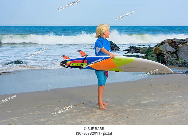 Young boy at beach, holding surfboard