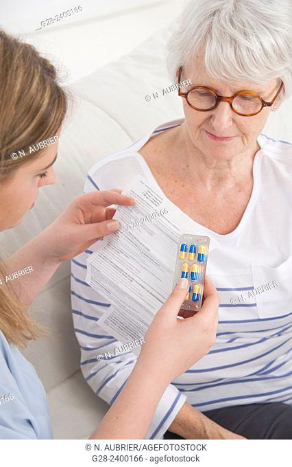 Young nurse or help or granddaughter reading prescription paper, and holding tablets, for patient or grandmother who is laughing in the background