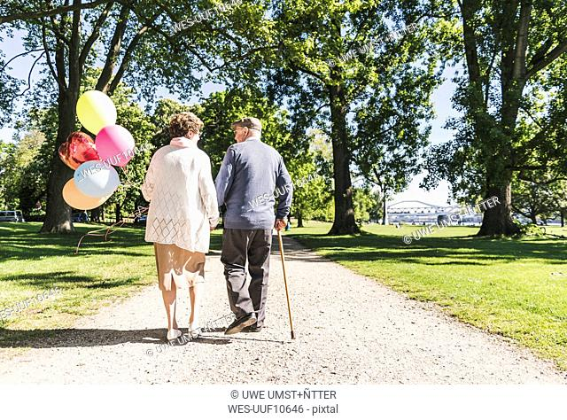 Back view of senior couple with balloons strolling in a park