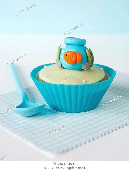 A cupcake with fondant icing and a goldfish bowl on the top