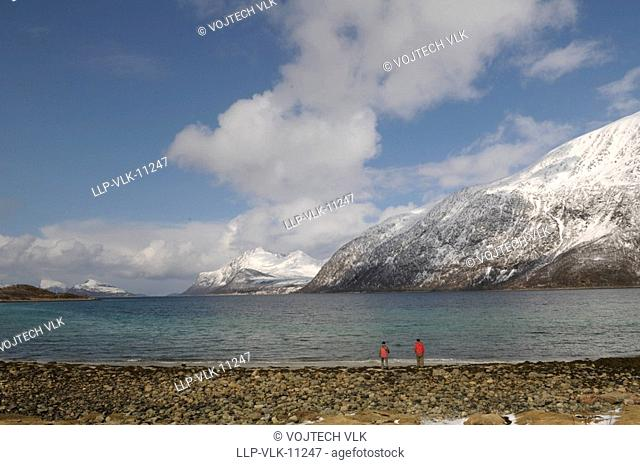 The stone beach, undisturbed surface of sea, snowy mountains on background and blue sky with clouds
