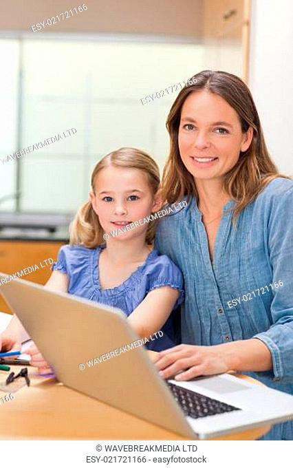 Portrait of a girl doing her homework while her mother is working with laptop