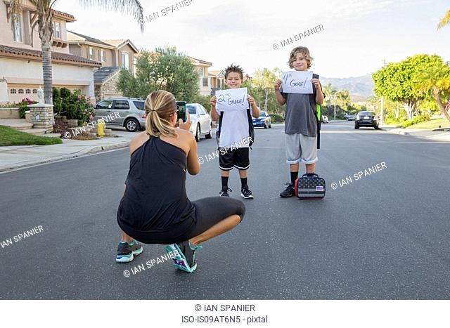 Mother photographing two schoolboy sons holding papers with handwritten school grade
