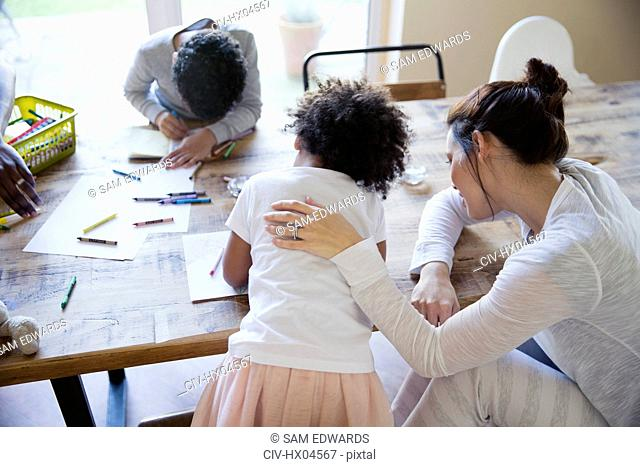 Mother and children coloring at dining table