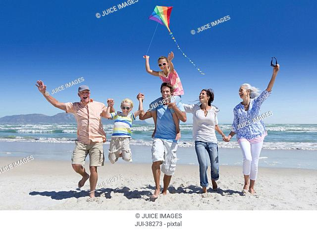 Happy multi-generation family with kite running and waving on sunny beach