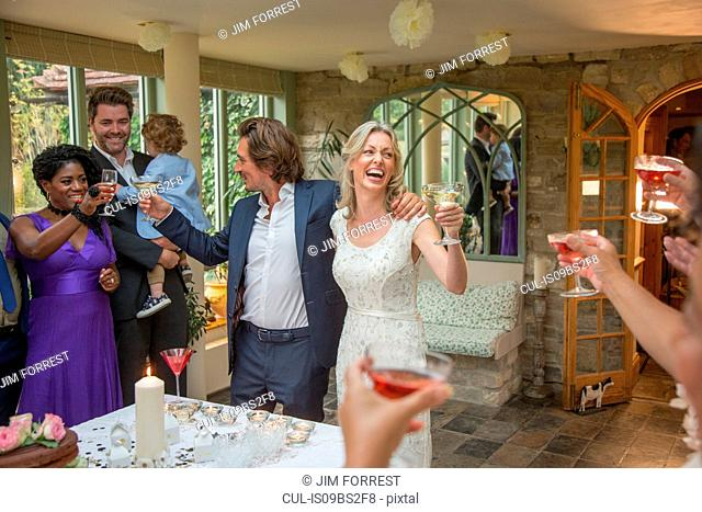 Wedding guests toasting to newlyweds at reception