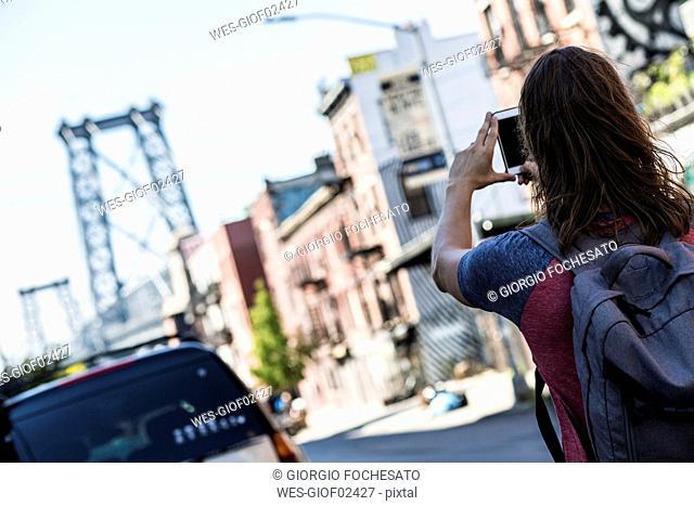 USA, New York City, man taking a picture of Williamsburg Bridge