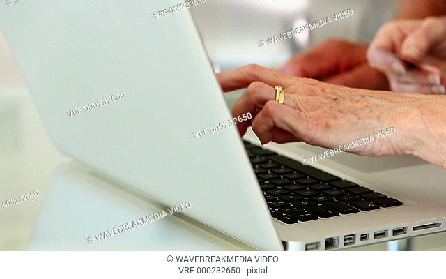 Senior couple using laptop to shop online at home in the kitchen