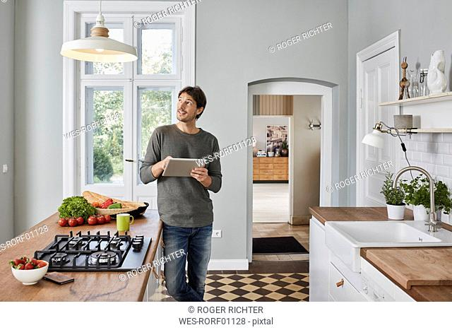 Man using tablet in kitchen looking at ceiling lamp