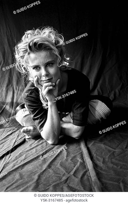Tilburg, Netherlands. Studio portrait of a young adult, blonde, female dancer, against a black background cloth. Shot on Analog Black & White film in 1995
