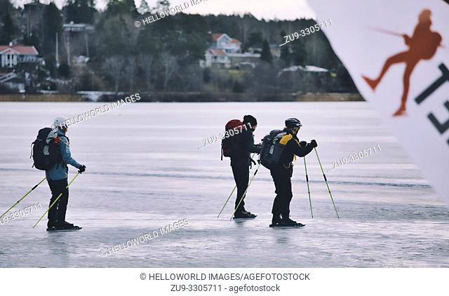Long distance ice skaters with ice poles on Lake Malaren with blurred logo of ice skater, Sigtuna, Sweden, Scandinavia