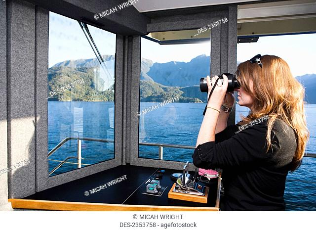 A Woman Views The Fiords Through Binoculars On The Real Journey Boat To Doubtful Sound; New Zealand
