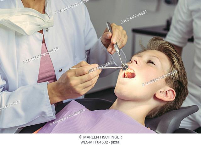 Dentist examining boy's teeth with dental instruments