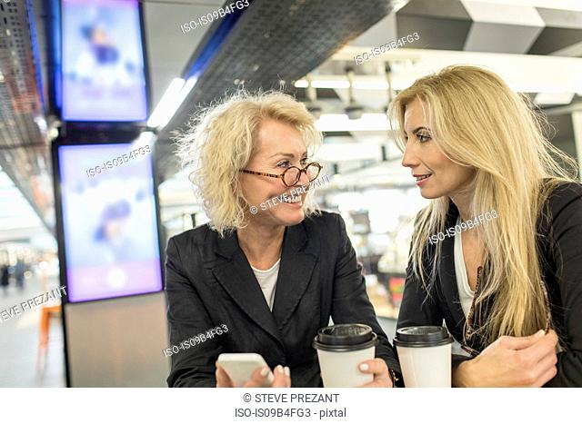 Two mature female friends chatting in shopping mall cafe
