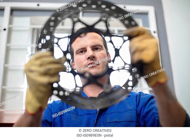 Car mechanic inspecting circular car part in repair garage