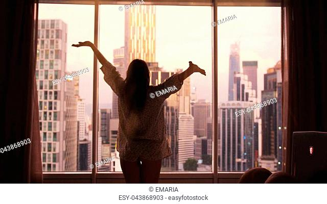 Slow motion. Young woman uncover the big window and looking out her apartment on the city buildings. Sunrise in the city
