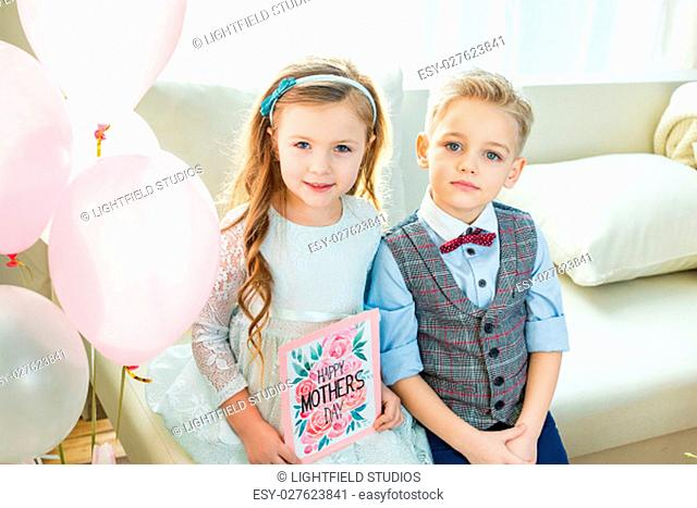 Cute little boy and girl holding Mothers Day greeting card and looking at camera