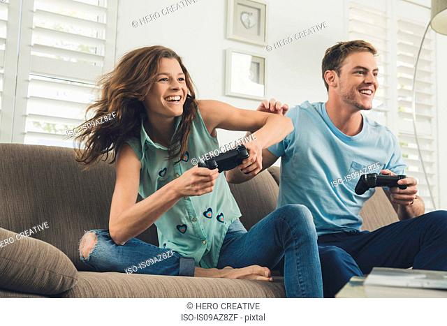 Couple on sofa using video game controller smiling
