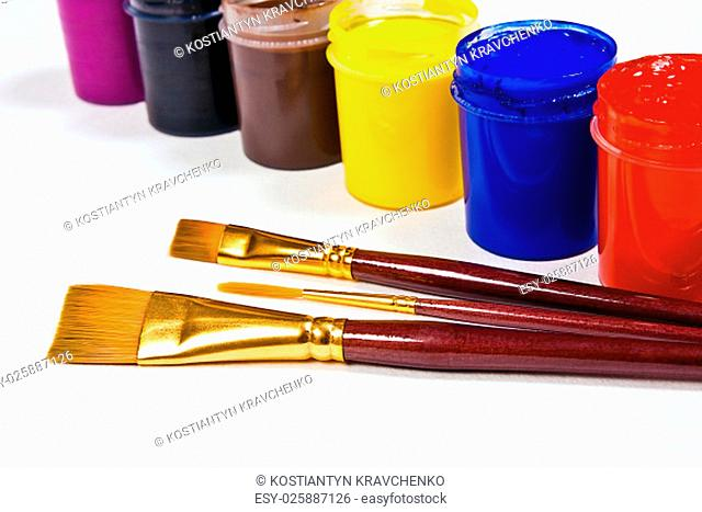 Bottles with gouache paints and different kinds of brushes for artistic paintings