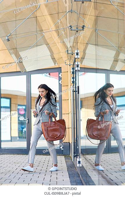 Businesswoman walking outdoors, using smartphone