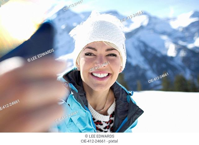 Smiling woman taking selfie in snow