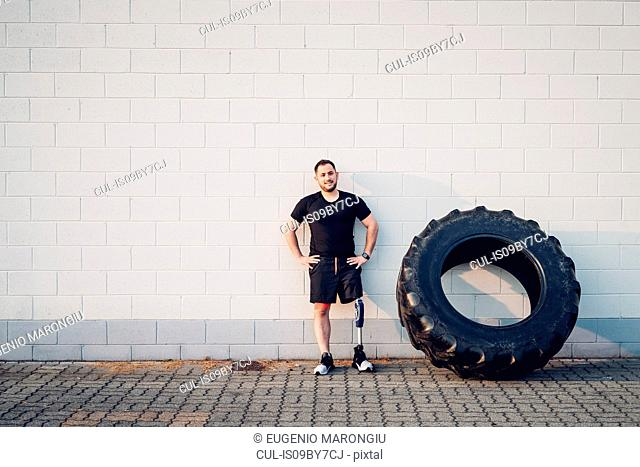 Man with prosthetic leg leaning on wall beside training tyre