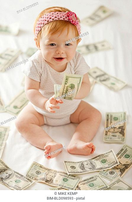 Caucasian baby girl playing with twenty dollar bills